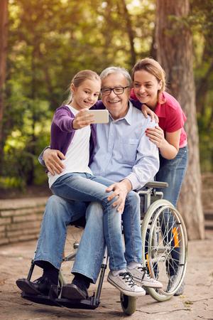公園 - 孫娘、車椅子の娘と無効になっている人の家族 selfie 時間 写真素材