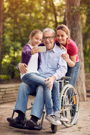 family selfie time in the park - granddaughter, daughter and disabled man in wheelchair Фото со стока