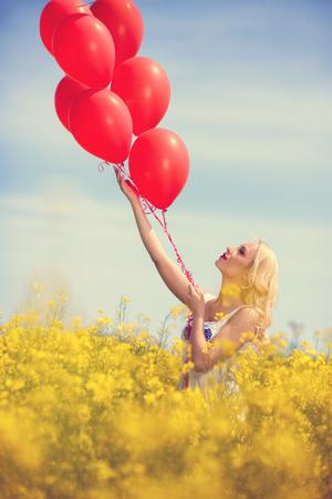 Meisje in het gele veld loslaten van een bos van rode ballonnen