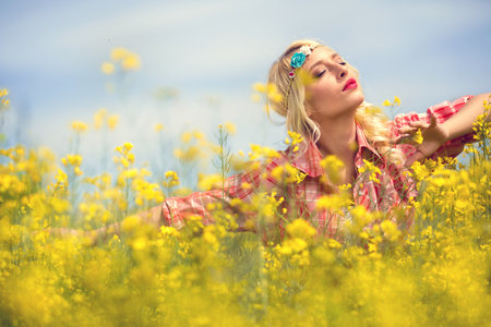 Young girl enjoy in blooming yellow field, concept freedom and enjoy Stock Photo