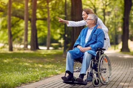 Verpleegster met iets aan oudere man op rolstoel in het park