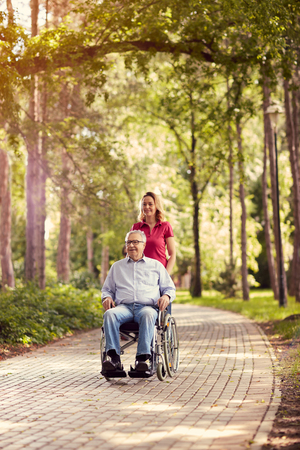 smiling daughter in the park pushing enjoying senior man in wheelchair 스톡 콘텐츠