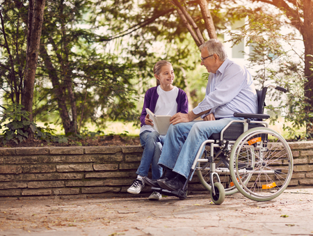 屋外の本を読んで彼の孫娘と共に時間を過ごす公園の車椅子で無効の祖父 写真素材