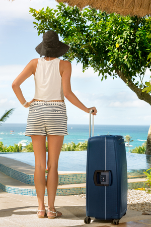 Female tourist arrived on summer vacation, standing with suitcase and looking in beautiful view