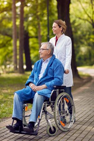 portrait of elderly man on wheelchair with caregiver nurse outdoor