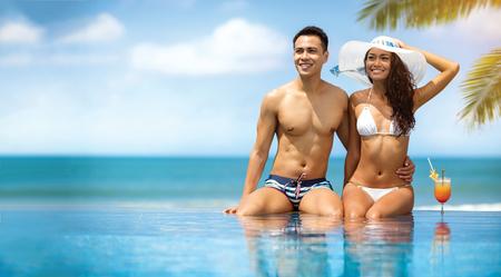 aantrekkelijk paar zonnebaden en aanhankelijk zijn zittend aan een zwembad