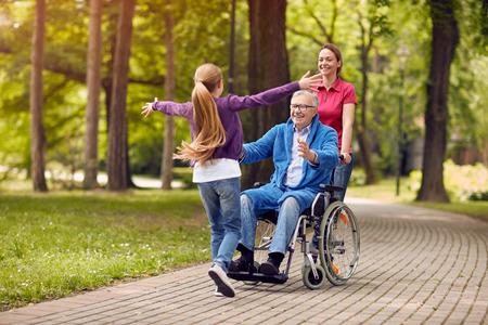 Avô desocupado alegre em cadeira de rodas acolhendo sua neta feliz Foto de archivo - 84902482