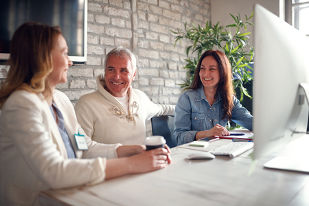 smiling business people working together at desk on computer in office
