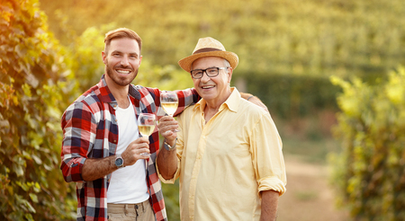 smiling father and son tasting white wine in vineyard