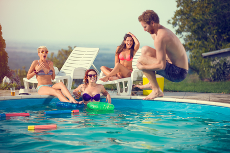 Male jump style bomb in open pool while girls admires him Stock Photo