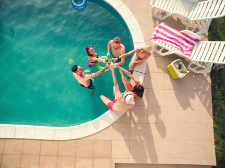 Young people toasting with bottles of bear in swimming pool at summer, top view