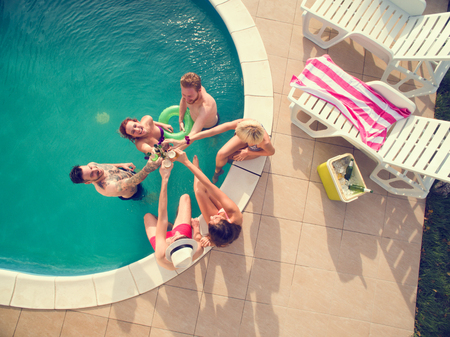 Top view of young cheerful girls and boys in swimming pool toasting with cold bear