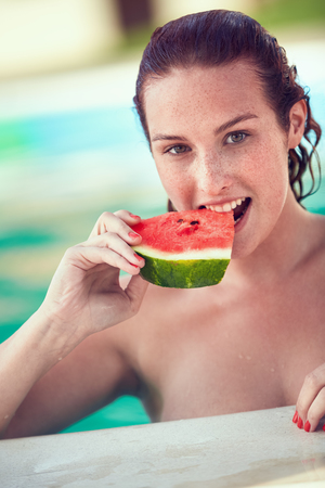 bather: Young bather female refreshing with watermelon in open pool at summer