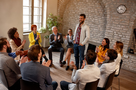 discussion business group- coworkers applauding man in group meeting