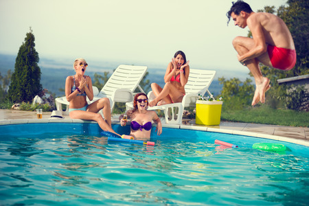 Young in pool scared look his male friend while jumps in open pool