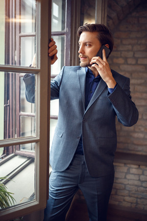 Businessman talking on cell phone in office while looking through window