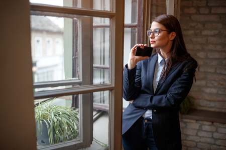 Pensive young woman standing near opening window in office