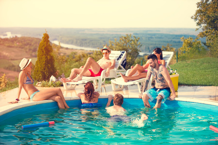 Young group enjoying in swimming pool at summer