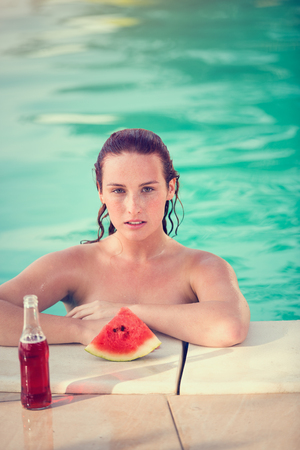 Portrait of young female bather in swimming pool with slice of watermelon and beverage by railing pool