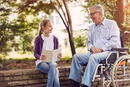 屋外の本を読んで彼の孫娘と共に時間を過ごす公園で無効の祖父 写真素材
