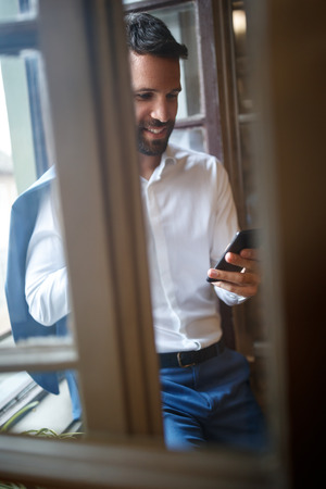 Handsome man in office calling friends at cell phone Stock Photo