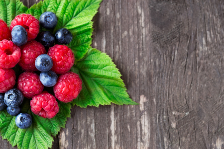 blueberry and raspberry with leaves on wooden table