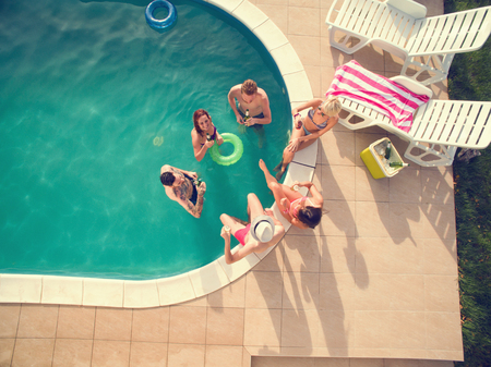 Group of young people in swimming pool drinking cold bear at summer
