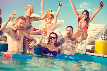 Happy boys and girls in pair enjoying in piscine with beverage in hands