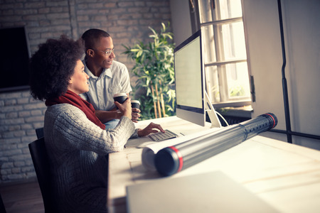 Woman with young manager at work on computer in office