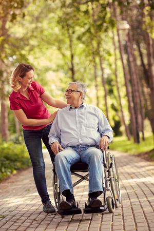 휠체어 야외에서 그녀의 장애인 된 웃는 아버지와 젊은 여자 스톡 콘텐츠