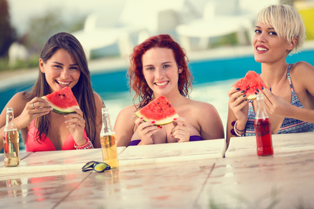 beautiful smiling girls posing by the  swimming pool with slice of watermelon