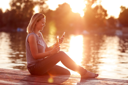 Young woman enjoy and refreshes by the river at sunset Stock Photo