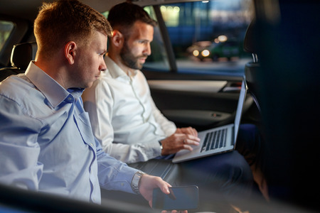 tired businesspeople work on late night in back seat of car Banque d'images