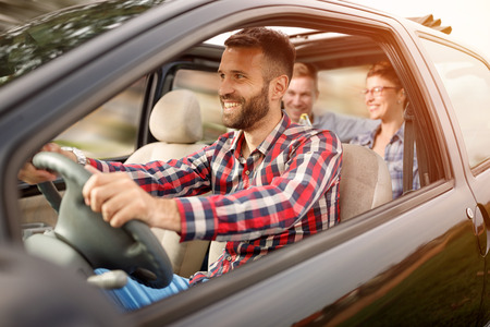 車で道路の旅行を楽しんでいる若い人たちのグループ 写真素材