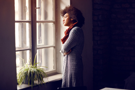 Female look through the window in office