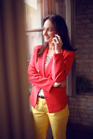 Smiling girl at job talking on cell phone Banque d'images