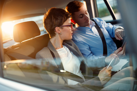 Conversation of two business people in driving car