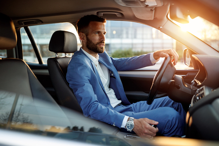 Attractive elegant man in business suit driving car