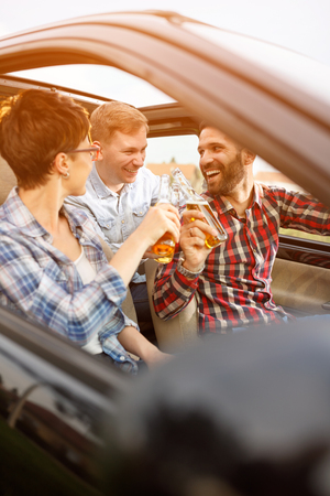 Group of young friends having fun in the car on road trip