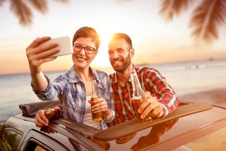 ビールを飲みながら一緒にビーチで selfie を取って楽しんで若い友人