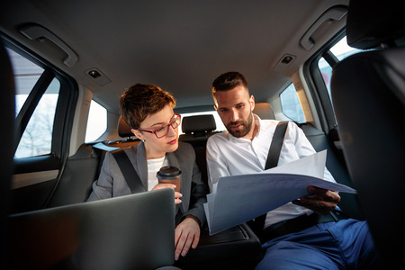 successful young business couple working together in back seat of car Standard-Bild