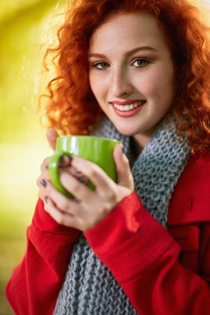 Young redhead girl drinking coffee outside in autumn
