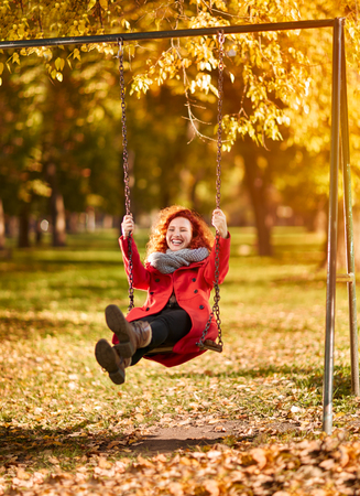 Young happy redhead woman on swing in park in autumn