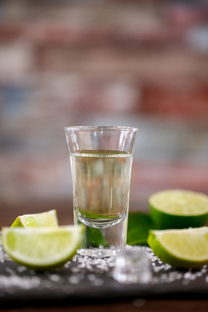 Mexican tequila shot with salt, lime and ice background