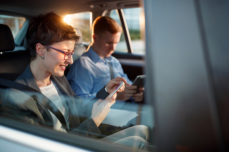smiling business woman calling smartphone number in driving car