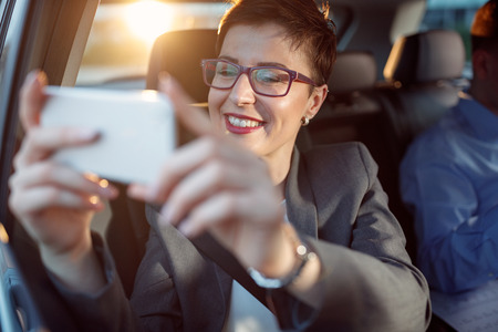 smiling business woman traveling and taking photos from a car
