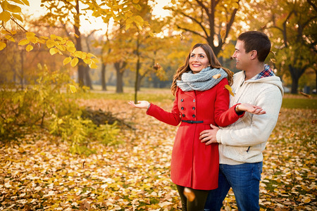 Romance between male and female in park with yellow leaves in autumn