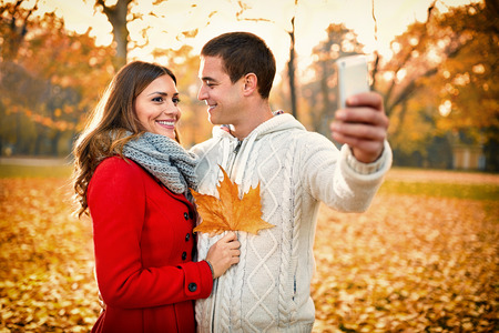 Male and female taking selfie in park in autumn Banque d'images