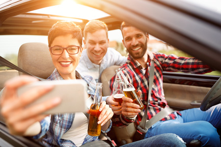 summer vacation, holidays, travel, road trip and people concept- happy friends taking selfie Banque d'images
