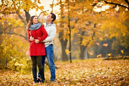 Girlfriend with boyfriend embraced walking in park in autumn